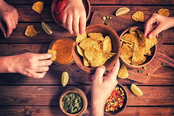 Snacks, viele Hände greifen zu Nachos | ÓNIRO essen